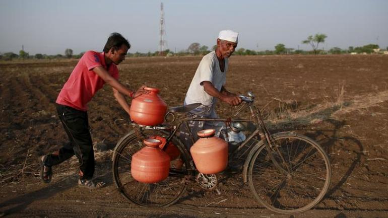Man carries pots to fill them with water in drought stricken Maharashtra